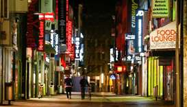 People walk down the empty Hohe Strasse shopping district during a night-time curfew, amid the coron