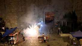 Palestinians react to a stun grenade fired by Israeli police during clashes at Damascus Gate on Layl