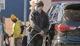 A person wearing a protective mask holds a fuel pump nozzle at a Chevron Corp gas station in San Fra