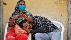 A man mourns after his father died due to the coronavirus disease outside a mortuary of a Covid hosp