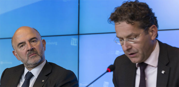 EU Economic and Financial Affairs, Taxation and Customs Commissioner Pierre Moscovici (L) listens to