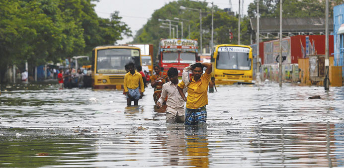 People wade through a flooded road in Chennai yesterday.