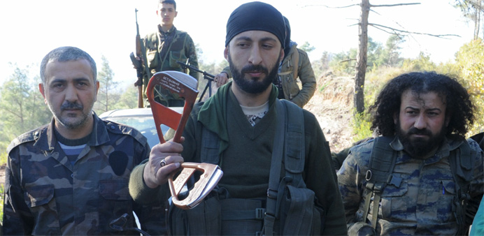 Deputy commander in a Syrian Turkmen brigade (C), holds handles believed to be parts of a parachute