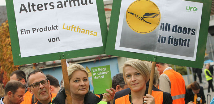 Cabin staff of German airline Lufthansa hold placards during a demonstration outside the airport in