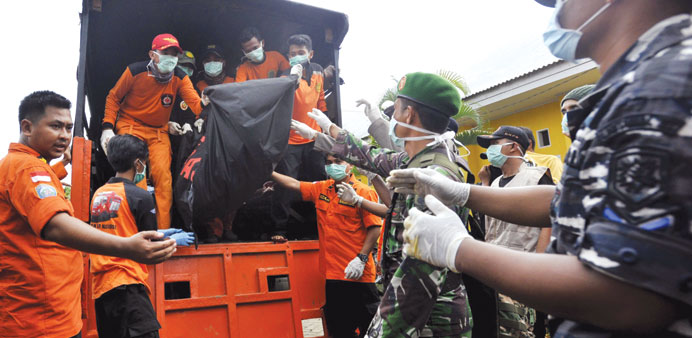 Rescue team members and soldiers unload the body of a victim of the sunken ferry Marina Baru at the