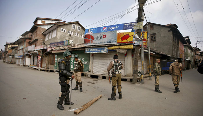 Indian security personnel stand guard along a deserted street during restrictions in Srinagar. Reute