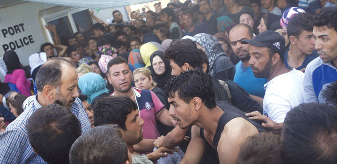 Afghan and Syrians scuffle yesterday over priority for a registration procedure at the port of Myti