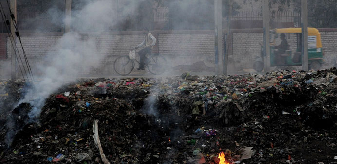 People pass by garbage that is dumped and burnt on the roadside in Faridabad