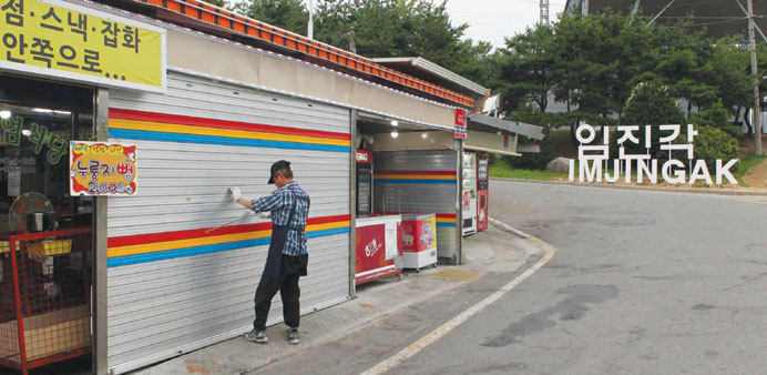A shopkeeper closes the shutters of his store near the demilitarised zone separating the two Koreas
