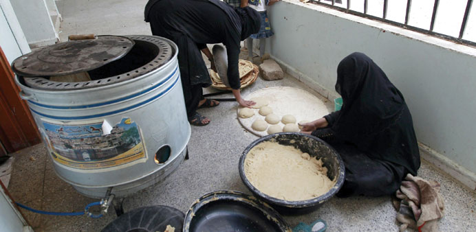 Displaced Yemeni women make bread at a school turned into a shelter in Sanaa.