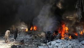 Men try to put out a fire at a market hit by air strikes in Idlib city, Syria