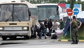 Migrants loads their belongings in a bus as they are evacuated from the makeshift camp