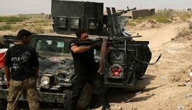 A member of Iraqi government forces aims his machine gun during an operation, in Fallujah's Shuhada
