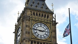 A Union flags flies at half-mast over Portcullis House in front of the clock face of Queen Elizabeth