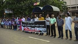 Bangladeshi activists hold the photos of activists, writers and bloggers who were murdered by uniden