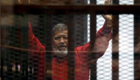 Deposed President Mohamed Mursi greets his lawyers and people from behind bars at a court