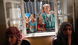 Palestinian children look through the window at mourners grieving the death of Aref Jaradat