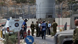 Israeli security forces inspect the scene of a stabbing attack at a checkpoint near the West Bank ci