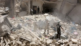 Syrian rescuers search the rubble of a destroyed buildings
