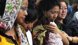 Nepalese relatives of 12 victims of a suicide bomb attack react as they pay their last respects alon