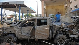 A man stands by a car wreckage in Mogadishu on the scene of the terror attack