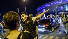 A Turkish police officer directs a passenger at Ataturk airport in Istanbul, after two explosions fo