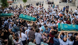 People carry the coffins of victims that were killed by the suicide bombing