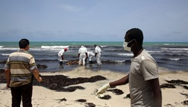 Libyan Red Crescent personnel retrieve the body of a migrant that washed up on a Libyan beach on the
