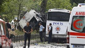 Police walk near a Turkish police bus which was targeted in a bomb attack in a central Istanbul dist