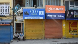 Nepalese men read the newspaper outside shuttered shops during a general strike called by a hardline