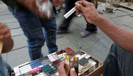 A street vendor sells cigarettes to a customer on a street in Jakarta