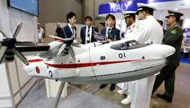 Military officials watch a model of Japan Maritime Self-Defense Forces US-2 search-and-rescue amphib