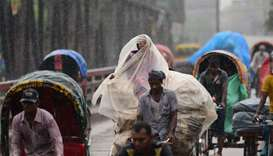 Bangladeshi rickshaw pullers make their way with commuters during a monsoon rain in Dhaka