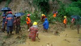 Bangladeshi fire fighters search for bodies after a landslide in Bandarban