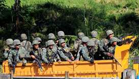 Government troops are seen onboard a truck driving along a main road of Amai Pakpak