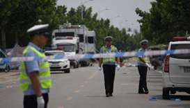 Police officers stand outside a kindergarten where an explosion killed 8 people and injured dozens a