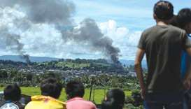 People watch as smoke billows from houses after aerial bombings by Philippine Air Force planes on mi