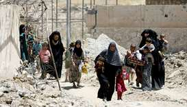 Displaced civilians walk towards the Iraqi Army positions after fleeing their homes due to clashes i