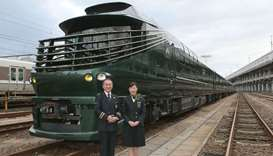 Members of the crew pose with the Twilight Express Mizukaze during its press preview in Osaka.