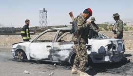 Afghan security forces inspect the exterior of a car after a suicide bomb blast in Gardez, Paktia Pr