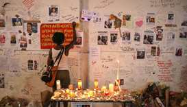 A woman writes on a wall covered with tributes to and pictures of the victims of the Grenfell apartm
