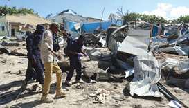 Somali policemen assess the scene of an attack on a government building in Mogadishu.