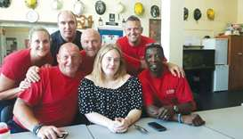 Singer Adele poses with firefighters at the Chelsea Fire Station. The singer paid an unexpected visi