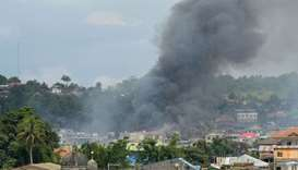 Smoke billows from houses after aerial bombings by Philippine Airforce planes on militants