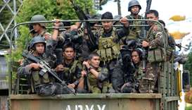 Members of the Philippine police special action force ride in an army truck on their way to Marawi