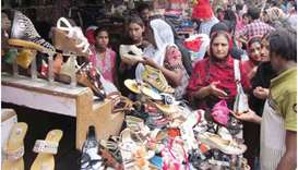 Women buy sandals at market ahead of Eid al-Fitr in Lahore.