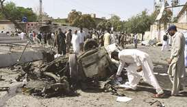 Security officials inspect the site of a powerful explosion that targeted a police vehicle in Quetta