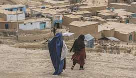 Nawzi Fakiri, left, and Afghan resident Anissa Azimi, walk through Zanabad on the outskirts of Kabul