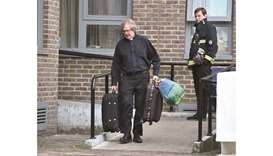 A vicar helps residents evacuate the Dorney Tower residential block in north London.