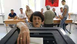 A wpman casts her ballot at a polling station in Tirana